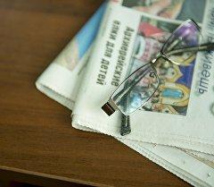 Очки и газеты на столе. Архивное фото
