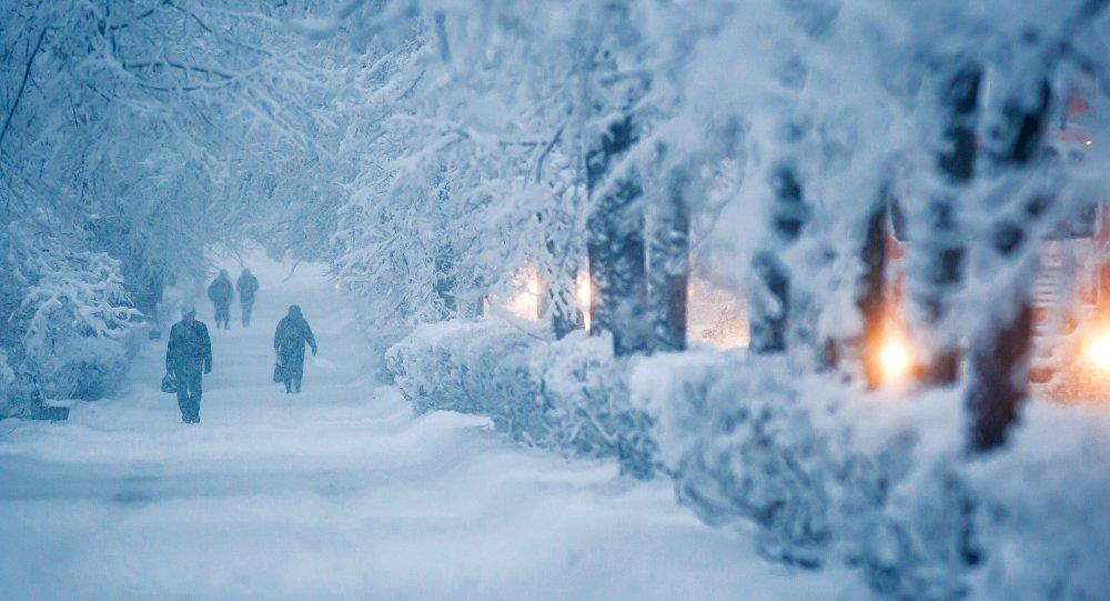 Прохожие идут по тротуару во время снегопада. Архивное