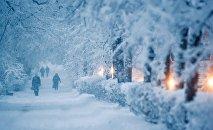Прохожие идут по тротуару во время снегопада. Архивное фото