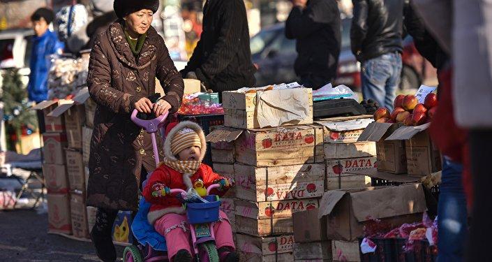 Женщина с ребенком на одном из рынков Бишкека. Архивное фото