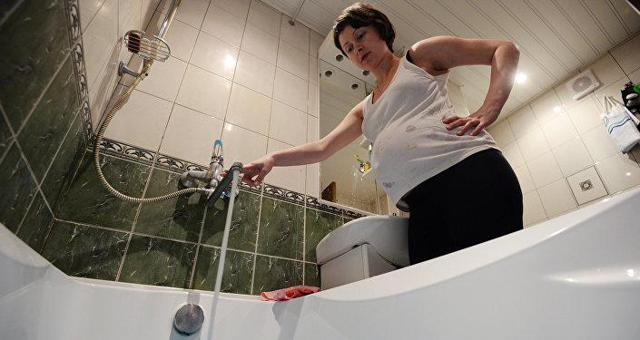 Женщина набирает воду в ванной комнате. Архивное фото