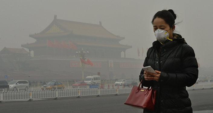 Женщина в защитной маске идет возле площади Тяньаньмэнь окутанный смогом, Китай. Архивное фото