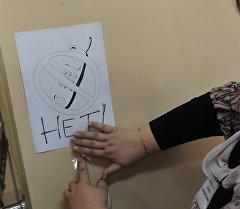 Учительница развешивает плакаты, напоминающие о запрете пользоваться мобильными телефонами при сдаче экзамена. Архивное фото