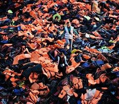 Лесбос аралындагы куткаруучу жилеттер арасында басып бараткан аял. Архив