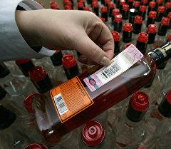 Сотрудник ликероводочного завода наклеивает акцизные марки на бутылки с продукцией. Архивное фото