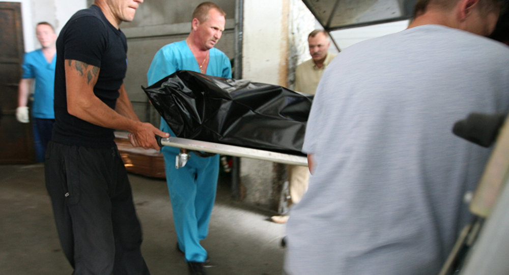 Сотрудники морга грузят труп в машину. Архивное фото