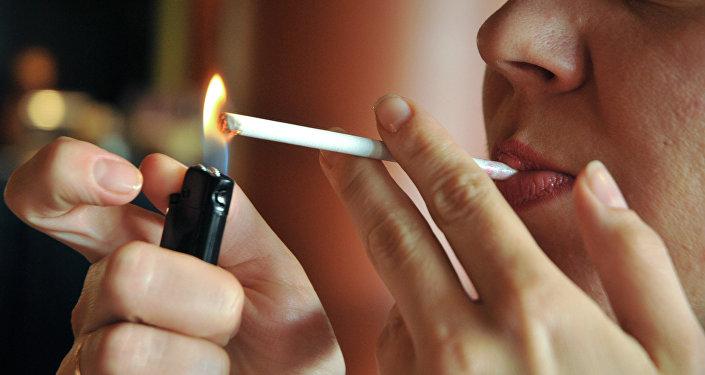 Девушка прикуривает сигарету. Архивное фото