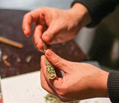 Мужчина заворачивает марихуану в бумагу. Архивное фото