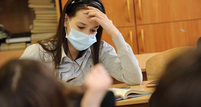 Ученица в медицинской маске во время занятий. Архивное фото