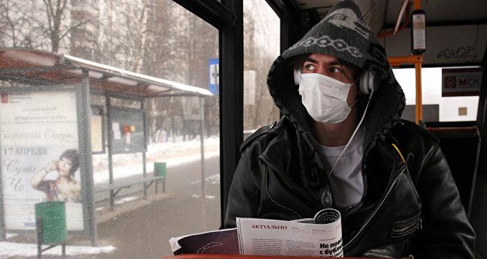 Молодой человек в защитной маске в общественном транспорте. Архивное фото