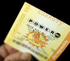 Мужчине держит лоторейный билет Powerball.