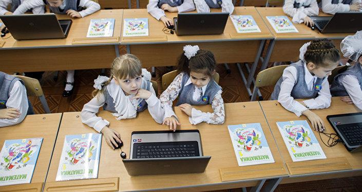 Ноутбук менен окуп жаткан окуучулар. Архив