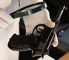 Криминалист проводит анализ огнестрельного оружия. Архивное фото