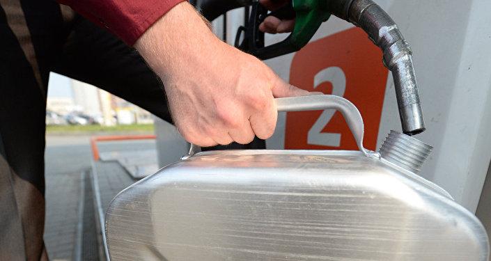 Автолюбитель заливает бензин в канистру. Архивное фото