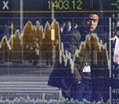 Отражение мужчины на электронной экране графика ценных бумаг в Токио, Япония.