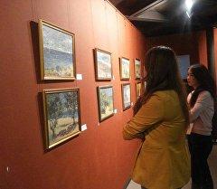 Посетители смотрят картины кыргызстанского художника на выставке в Красноярске.