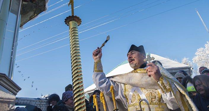 Священник обливает священной водой на церковном празднике крещения Христа. Архивное фото