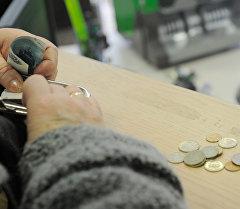 Женщина расплачивается в кассе банка. Архивное фото