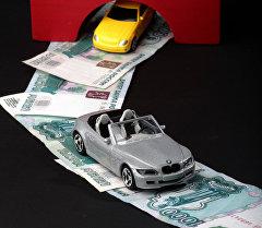 Денежные купюры и игрушечный автомобиль. Архивное фото
