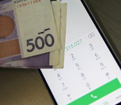Мобильный телефон и деньги на столе. Архивное фото