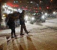 Вашингтон шаарынын көчөсүндө кар учурунда кетип бараткан адамдар.