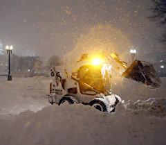 Сотрудник коммунальной службы убирает снег на снегоуборочной машине в США.