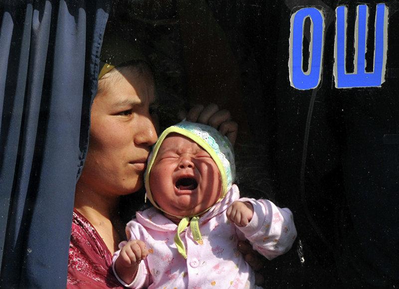 Мать и ее ребенок сидят в автобусе  в городе Ош 23 июня 2010 года.