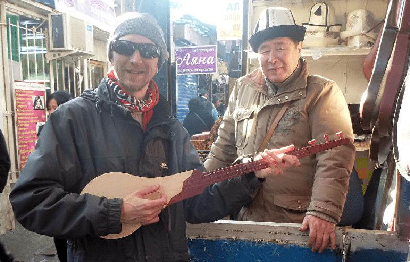 Известный путешественник Джонни Блэйр с комузом в одном из рынков Бишкека
