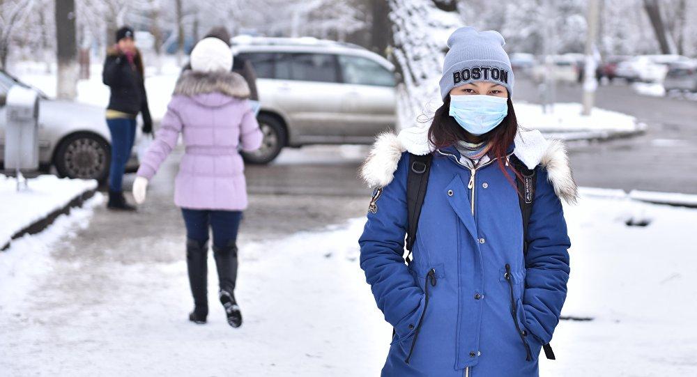 Девушка в защитной маске идет по улице Бишкека. Архивное фото