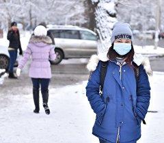 Девушка в медицинской маске идет по улице Бишкека. Архивное фото