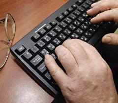 Компьютерде иштеп жаткан адам. Архив