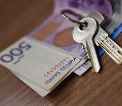 Национальная валюта Кыргызстана и ключи на столе. Архивное фото