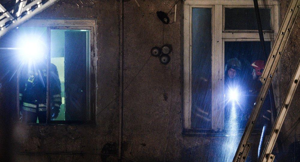 Сотрудники пожарно-спасательных подразделений МЧС на месте пожара в швейном цеху по производству подушек.