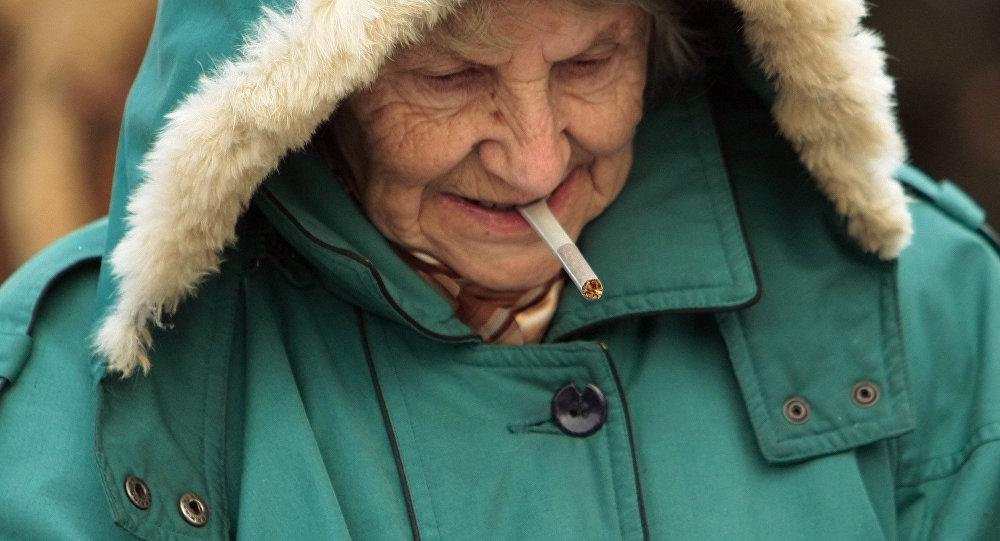 Пенсионерка прикуривает сигарету. Архивное фото