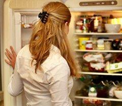 Девушка возле холодильника с продуктами. Архивное фото