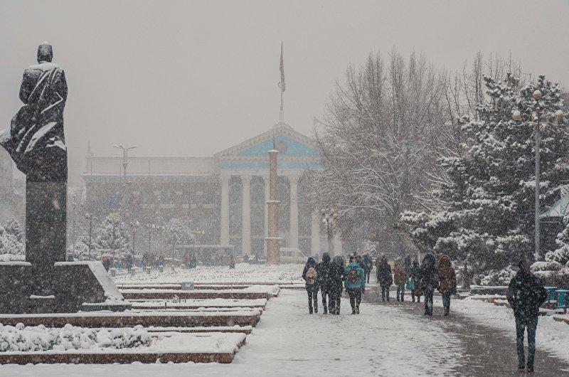 Молодые люди идут по Аллее молодежи возле памятника Шабдан баатыру во время снегопада в Бишкеке