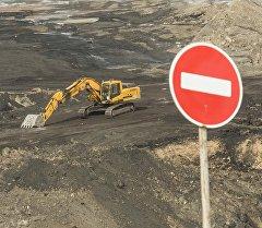 Запрещающий въезд дорожный знак на фоне экскаватора. Архивное фото