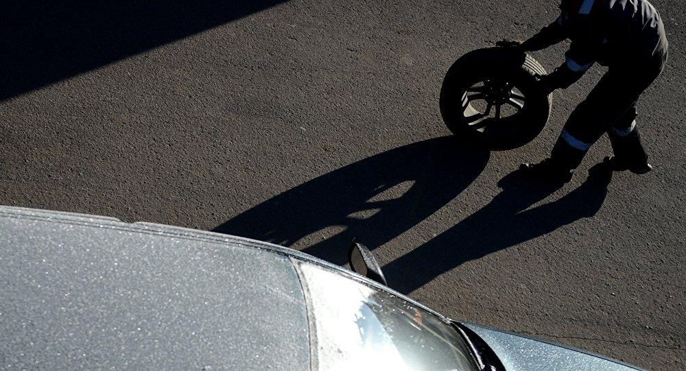 Мужчина с шиной от автомобиля. Архивное фото