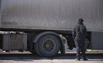 Водитель большегрузной фуры у автодороги на границе Кыргызстана с Казахстаном. Архивное фото