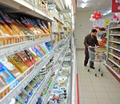 Посетитель проходит с тележкой вдоль стеллажей с продуктами. Архивное фото