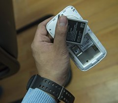 Мужчина держит телефон с батарейкой. Архивное фото