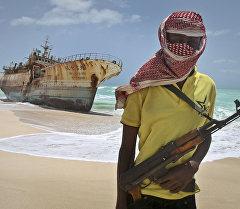 Пират с автоматом на берегу океана. Архивное фото