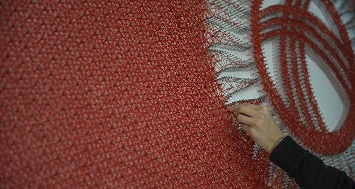 Кыргызстандын желегин жиптен тартып жаткан кыз