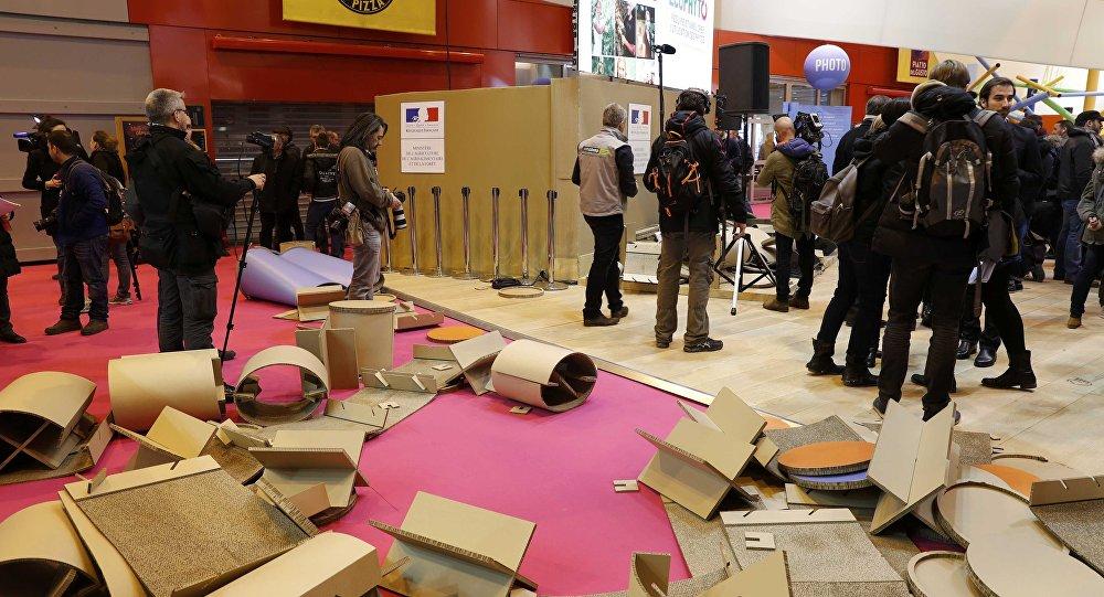 Журналисты на месте беспорядков на международной сельскохозяйственной выставке в Париже, где протестующие снесли стенд министерства сельского хозяйства.