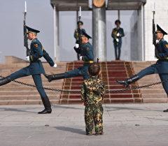 Трехлетний мальчик Сердар Таалайбеков марширует у флагштока, где караульные у поста №1 охраняют Национальный флаг КР в центральной площади Ала-Тоо, Бишкек. Архивное фото