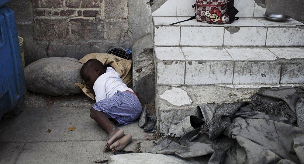 Гаитидеги көчөдө жаткан бала. Архивдик сүрөт