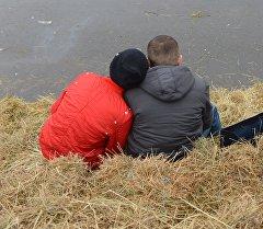 Молодые люди сидят на сеновале для влюбленных. Архивное фото
