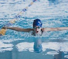 Мальчик плавает в бассейне во время соревнований. Архивное фото