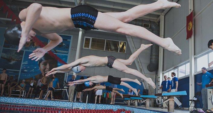 Участники соревнований прыгают в бассейн. Архивное