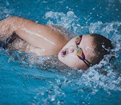 Мальчик плавает в бассейне во время соревнований